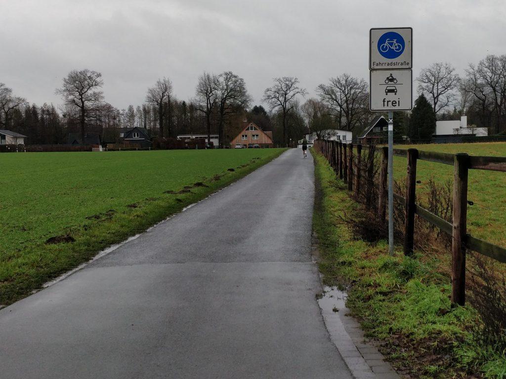 """Das Bild zeigt den Anfang der Fahrradstraße """"Am Hohen Ufer"""". Es zeigt eine nasse, asphaltierte Straße, die in die Tiefe des Bildes führt. Auf der linken Seite der Straße ist ein grüner Acker. Auf der rechten Seite steht das Fahrradstraßen Bild mit dem Zusatz, KFZ frei. Rechts der Straße verläuft ein Weidezaun. Im Hintergrund sind Wohnhäuser und Bäume zu sehen."""