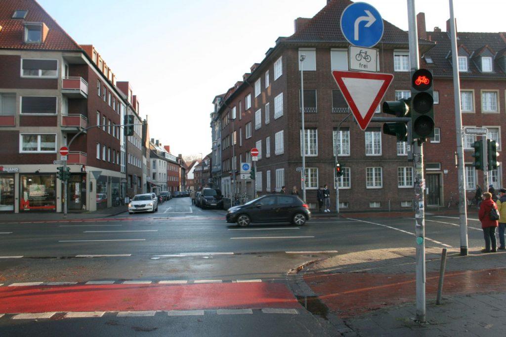 Auf dem Bilde treffen die Straße Schlossplatz und Frauenstraße auf einer T-Kreuzung aufeinander. Die Fahrradstraße Frauenstraße ist mit einem Fahrradstraßen Schild ausgeschildert und rechts und links von parkenden Autos gesäumt.