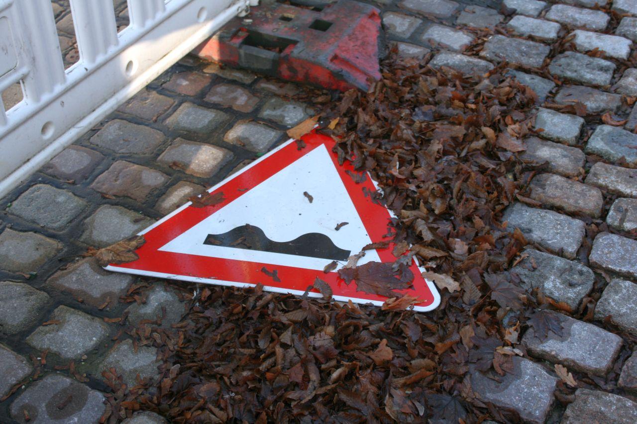 Ein Verkehrszeichen 112 (Warnung vor unebener Fahrbahn) liegt auf Kopfsteinpflaster in nassem Laub.